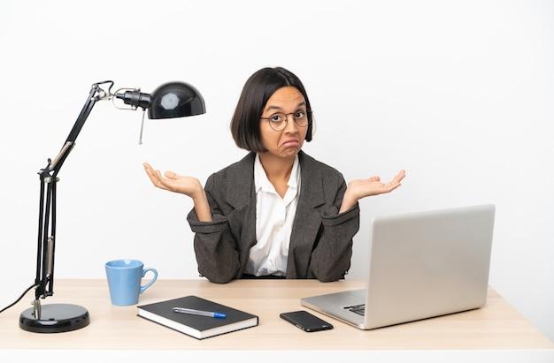 Jonge zakenvrouw van gemengd ras die op kantoor werkt en twijfelt terwijl ze handen opsteekt
