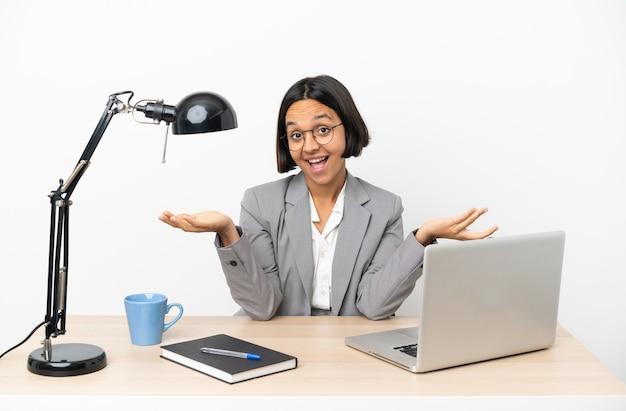 Jonge zakenvrouw van gemengd ras die op kantoor werkt en twijfelt