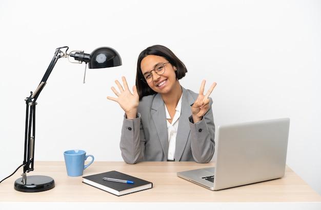 Jonge zakenvrouw van gemengd ras die op kantoor werkt en zeven met vingers telt