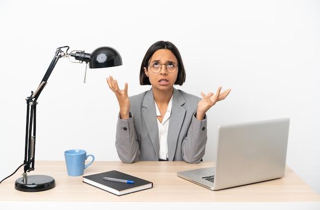 Jonge zakenvrouw van gemengd ras die op kantoor werkt gestrest overweldigd