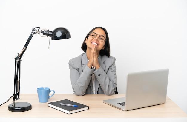 Jonge zakenvrouw van gemengd ras die op kantoor werkt, houdt de palm bij elkaar. persoon vraagt om iets
