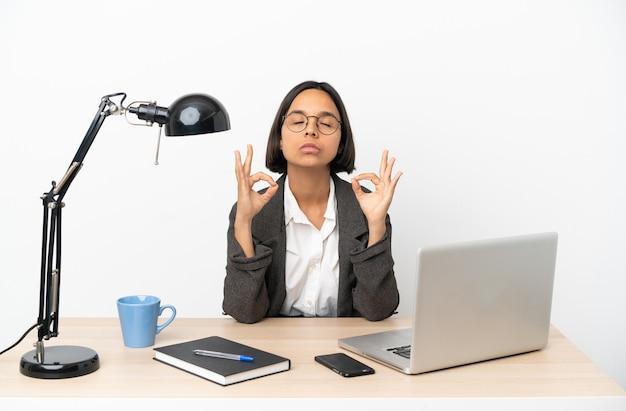 Jonge zakenvrouw van gemengd ras die op kantoor werkt in zen pose