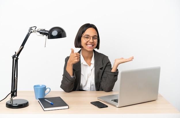 Jonge zakenvrouw van gemengd ras die op kantoor werkt met copyspace denkbeeldig op de palm om een advertentie in te voegen en met duimen omhoog