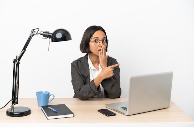 Jonge zakenvrouw van gemengd ras die op kantoor werkt met een verrassende uitdrukking terwijl ze naar de zijkant wijst Premium Foto