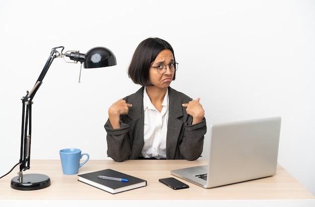 Jonge zakenvrouw van gemengd ras die op kantoor werkt, trots en zelfvoldaan