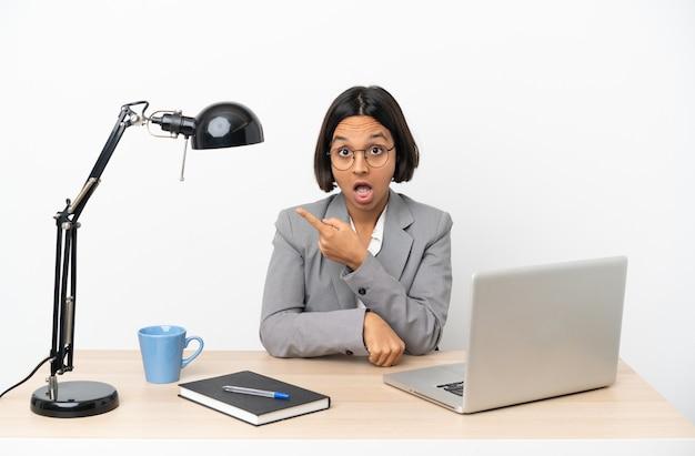 Jonge zakenvrouw van gemengd ras die op kantoor werkt, verrast en wijst naar de kant