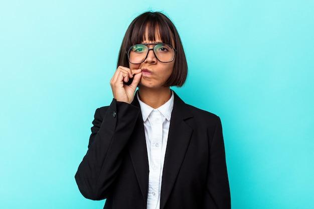 Jonge zakenvrouw van gemengd ras geïsoleerd op een blauwe achtergrond met vingers op de lippen die een geheim bewaren.