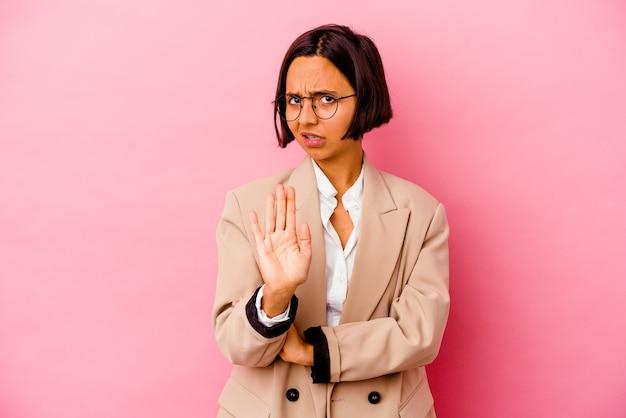 Jonge zakenvrouw van gemengd ras geïsoleerd op roze achtergrond die geschokt is vanwege een dreigend gevaar