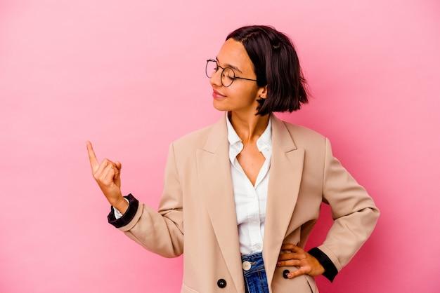 Jonge zakenvrouw van gemengd ras geïsoleerd op roze achtergrond die met de vinger naar je wijst alsof uitnodigend dichterbij komt.