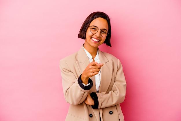 Jonge zakenvrouw van gemengd ras geïsoleerd op roze achtergrond die met vingers naar voren wijst.