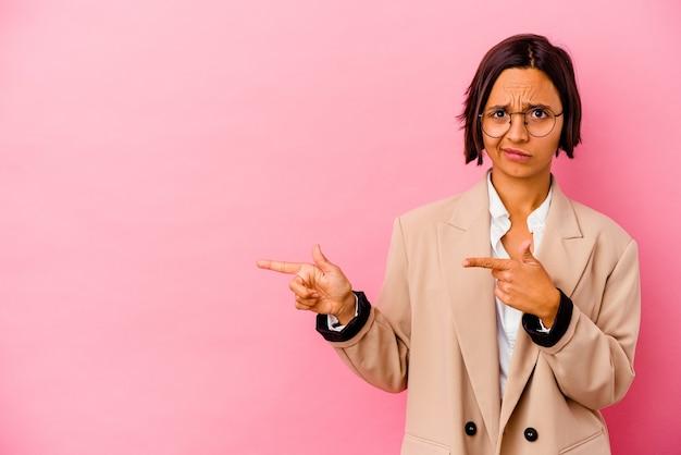 Jonge zakenvrouw van gemengd ras geïsoleerd op roze achtergrond geschokt wijzend met wijsvingers naar een kopieerruimte.