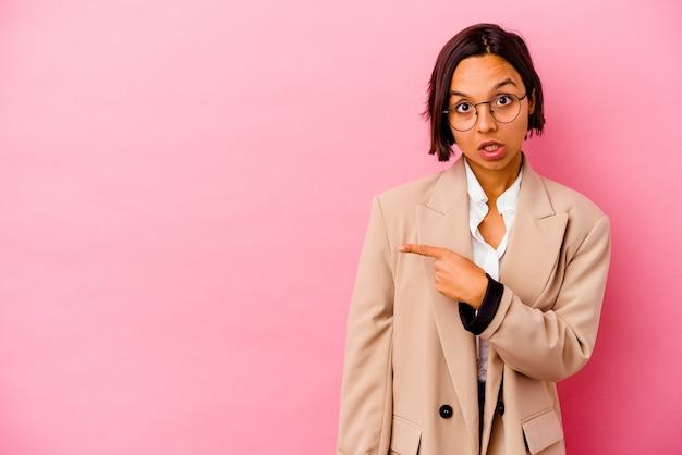 Jonge zakenvrouw van gemengd ras geïsoleerd op roze achtergrond glimlachend en opzij wijzend, iets tonend op lege ruimte.