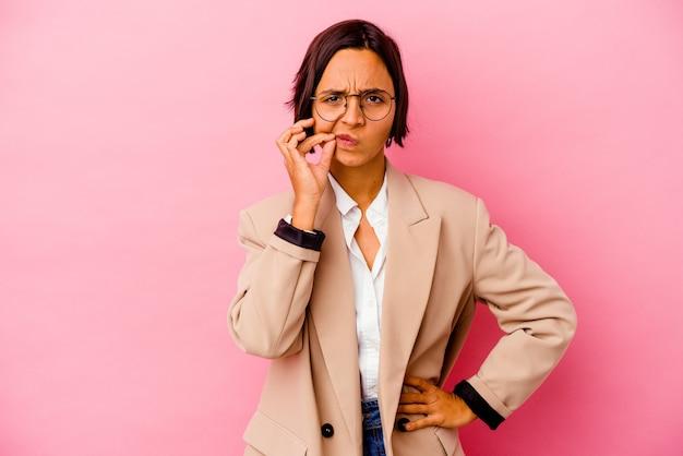 Jonge zakenvrouw van gemengd ras geïsoleerd op roze achtergrond met vingers op lippen die een geheim bewaren.