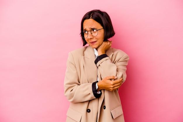 Jonge zakenvrouw van gemengd ras geïsoleerd op roze achtergrond verward, voelt zich twijfelachtig en onzeker.