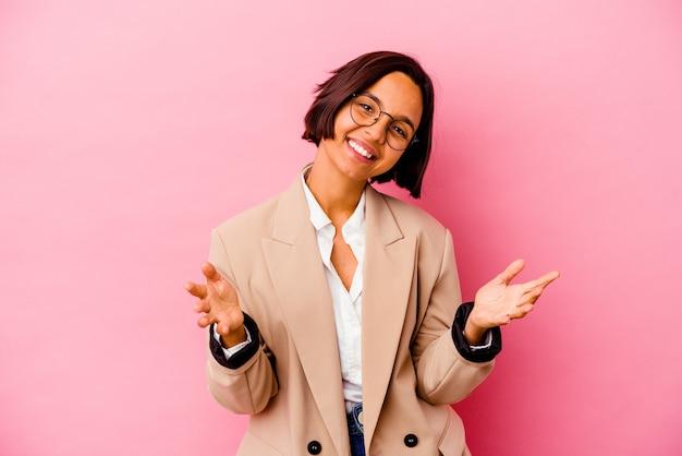 Jonge zakenvrouw van gemengd ras geïsoleerd op roze achtergrond voelt zich zelfverzekerd en geeft een knuffel aan de camera.