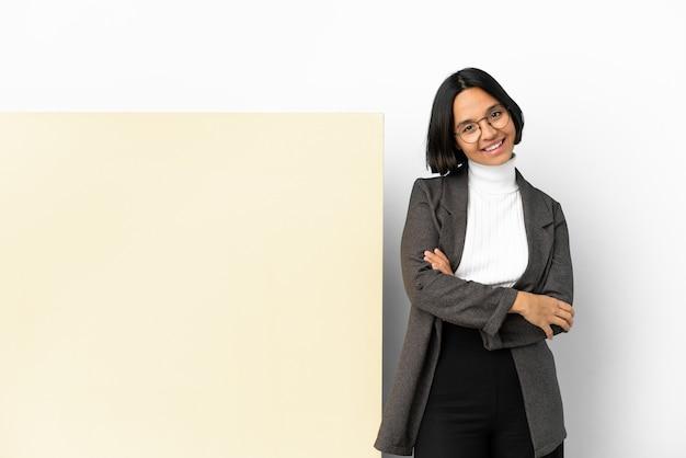Jonge zakenvrouw van gemengd ras met een groot spandoek over geïsoleerde achtergrond met gekruiste armen en vooruitkijkend