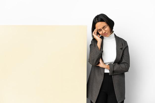 Jonge zakenvrouw van gemengd ras met een groot spandoek over geïsoleerde achtergrond met hoofdpijn