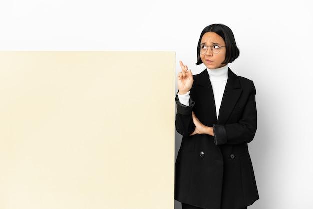Jonge zakenvrouw van gemengd ras met een groot spandoek over geïsoleerde achtergrond met vingers die kruisen en het beste wensen