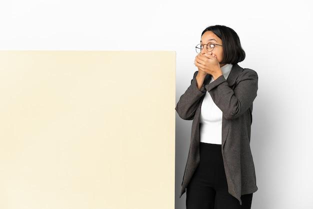 Jonge zakenvrouw van gemengd ras met een grote banner geïsoleerde achtergrond die de mond bedekt en naar de zijkant kijkt