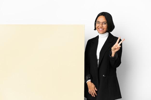Jonge zakenvrouw van gemengd ras met een grote banner geïsoleerde achtergrond die lacht en een overwinningsteken toont