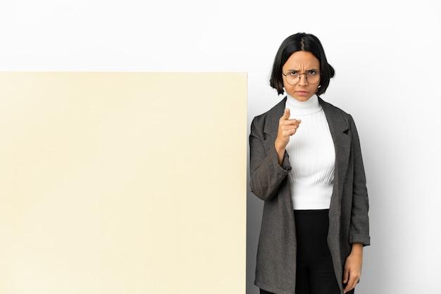 Jonge zakenvrouw van gemengd ras met een grote banner geïsoleerde achtergrond gefrustreerd en naar voren wijzend