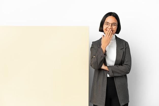 Jonge zakenvrouw van gemengd ras met een grote banner geïsoleerde achtergrond gelukkig en lachend die de mond bedekt met de hand
