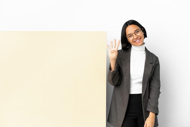 Jonge zakenvrouw van gemengd ras met een grote banner geïsoleerde achtergrond gelukkig en vier tellen met vingers