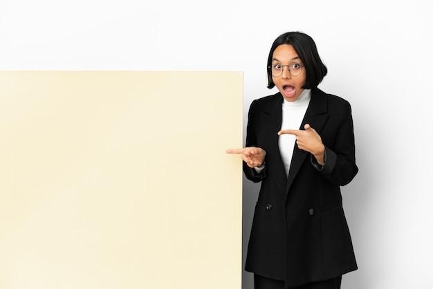 Jonge zakenvrouw van gemengd ras met een grote banner geïsoleerde achtergrond verrast en wijzende kant