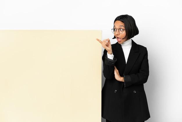 Jonge zakenvrouw van gemengd ras met een grote banner over een geïsoleerde achtergrond die de oplossing wil realiseren terwijl ze een vinger opsteekt