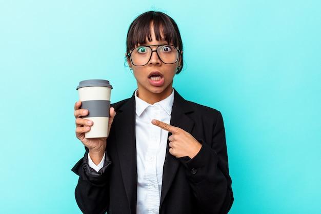 Jonge zakenvrouw van gemengd ras met een kopje koffie geïsoleerd op een blauwe achtergrond die naar de zijkant wijst