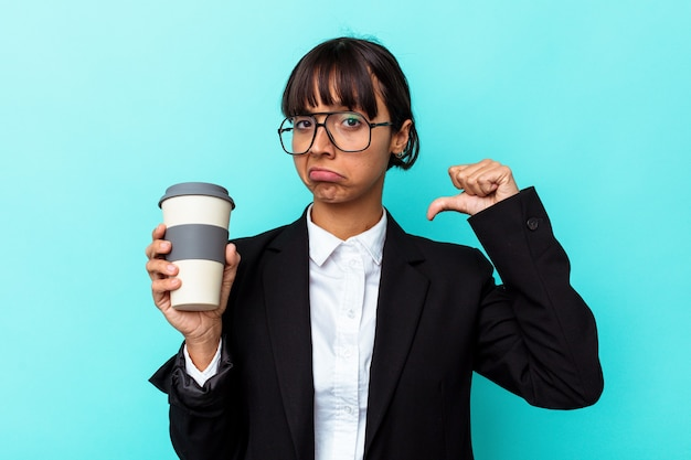 Jonge zakenvrouw van gemengd ras met een kopje koffie geïsoleerd op een blauwe achtergrond voelt zich trots en zelfverzekerd, een voorbeeld om te volgen.