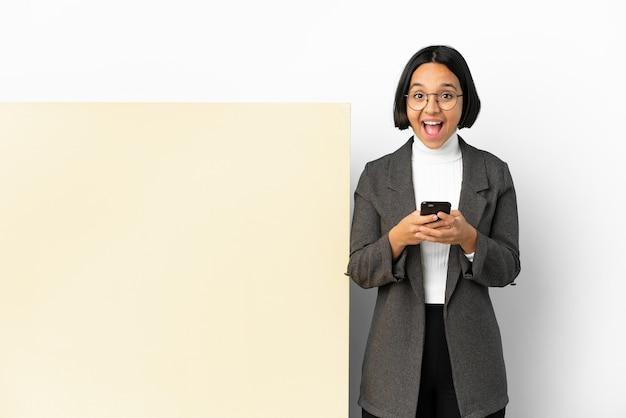 Jonge zakenvrouw van gemengd ras met met een grote banner over geïsoleerde achtergrond verrast en een bericht verzendend