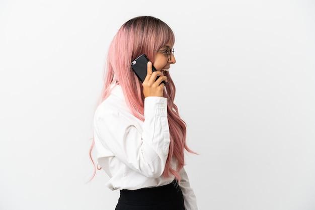 Jonge zakenvrouw van gemengd ras met roze haar die een mobiel vasthoudt op een roze achtergrond die lacht in zijpositie