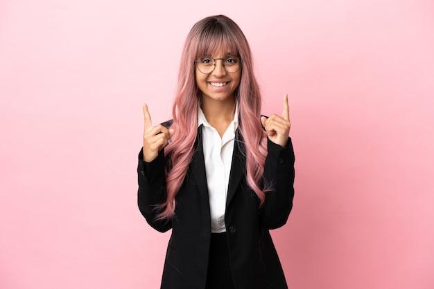 Jonge zakenvrouw van gemengd ras met roze haar geïsoleerd op een roze achtergrond die een geweldig idee benadrukt