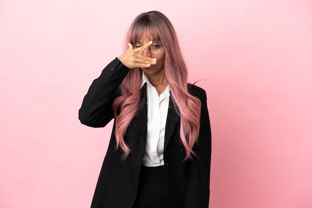 Jonge zakenvrouw van gemengd ras met roze haar geïsoleerd op een roze achtergrond die ogen bedekt met de handen en glimlacht