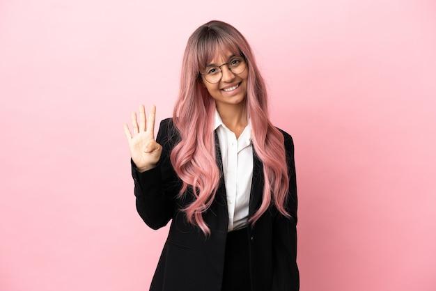 Jonge zakenvrouw van gemengd ras met roze haar geïsoleerd op roze achtergrond gelukkig en vier tellen met vingers