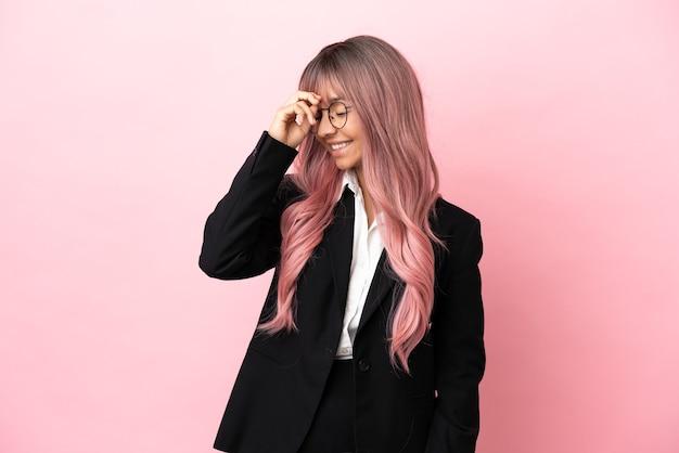 Jonge zakenvrouw van gemengd ras met roze haar geïsoleerd op roze achtergrond heeft iets gerealiseerd en heeft de oplossing voor ogen
