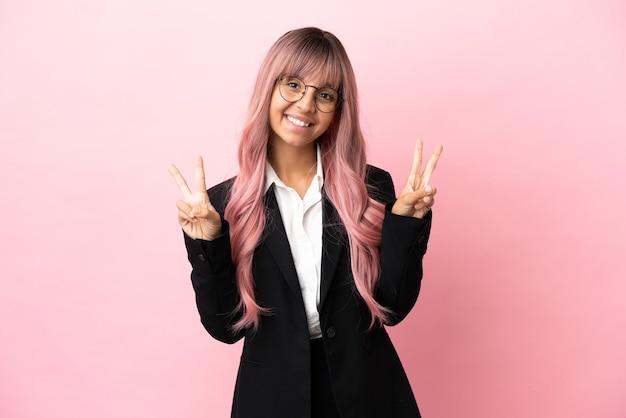 Jonge zakenvrouw van gemengd ras met roze haar geïsoleerd op roze achtergrond met overwinningsteken met beide handen