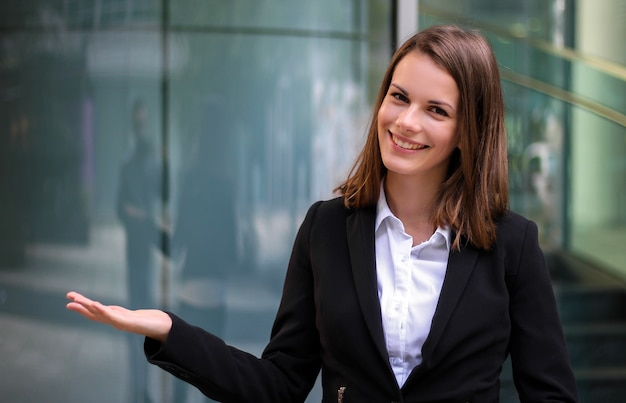Jonge zakenvrouw verwelkomen u in een moderne stad instelling