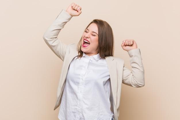 Jonge zakenvrouw viert een speciale dag, springt en heft de armen op met energie.