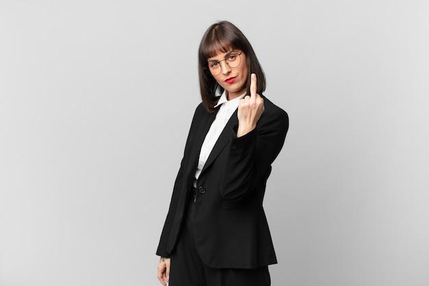 Jonge zakenvrouw voelt zich boos, geïrriteerd, opstandig en agressief, draait de middelvinger om en vecht terug