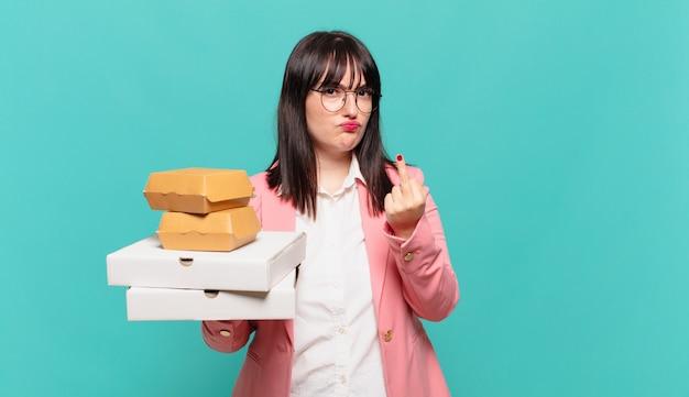 Jonge zakenvrouw voelt zich boos, geïrriteerd, opstandig en agressief, draait de middelvinger om, vecht terug