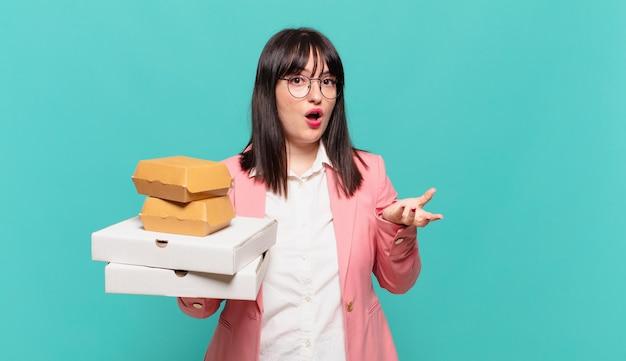 Jonge zakenvrouw voelt zich extreem geschokt en verrast, angstig en in paniek, met een gestresste en geschokte blik