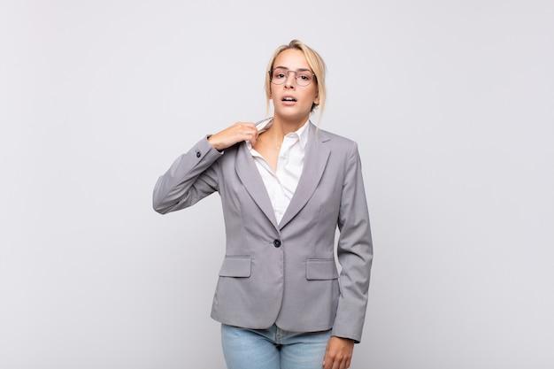 Jonge zakenvrouw voelt zich gestrest, angstig, moe en gefrustreerd, trekt de hals van het shirt aan, kijkt gefrustreerd door het probleem