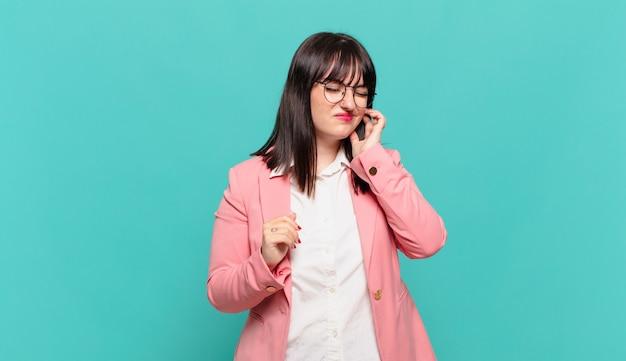 Jonge zakenvrouw voelt zich gestrest, gefrustreerd en moe, wrijft over pijnlijke nek, met een bezorgde, verontruste blik