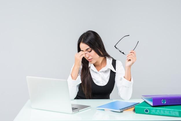 Jonge zakenvrouw voelt zich moe en houdt het hoofd vast aan het bureau dat op wit wordt geïsoleerd