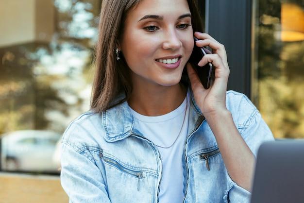 Jonge zakenvrouw werken op open terras thuis, zit achter laptop, smartphone in haar hand houden.