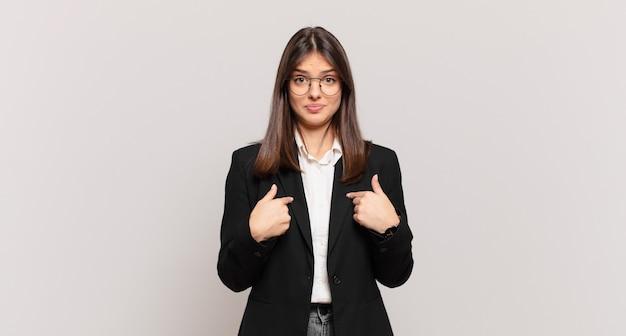 Jonge zakenvrouw wijst naar zichzelf met een verwarde en vragende blik, geschokt en verrast om gekozen te worden