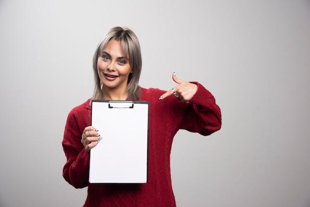 Jonge zakenvrouw wijzend op klembord op grijze achtergrond.