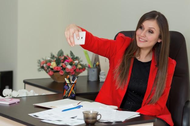 Jonge zakenvrouw wordt gefotografeerd op een smartphone in kantoor.